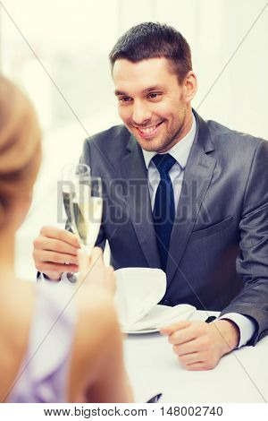 restaurant, couple and holiday concept - smiling man with glass of champagne looking at wife or girlfriend at restaurant