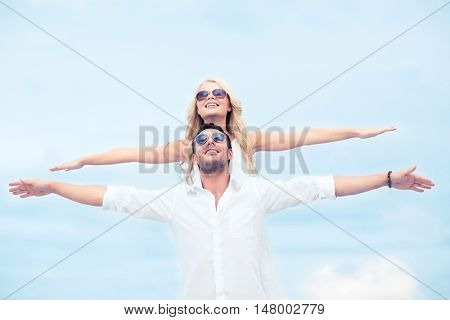 summer holidays and dating concept - couple holding hands up at sea side