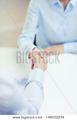 business and office concept - businesswoman and businessman shaking hands in office