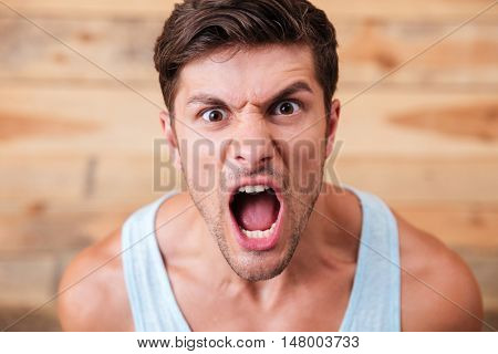Portrait of a young casual man screaming isolated on a wooden background