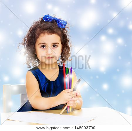 Cute little girl in blue dress, holds a lot of pencils . She paints at a table in a Montessori kindergarten.Blue winter background with white snowflakes.