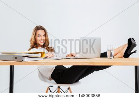 Cheerful young businesswoman sitting and using laptop with legs on table over white background