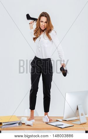 Full length of angry young businesswoman standing on table and throwing her shoes over white background