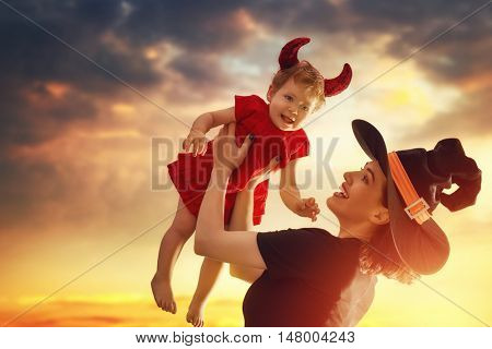 Happy halloween! A mother and her baby daughter in in masquerade dress. Woman in witch costume and baby in devil outfit.