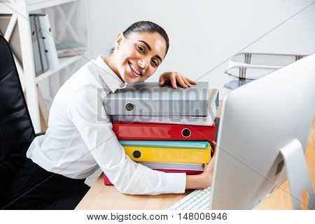 Cheerful smiling businesswoman laying head on the stack of colorful folders while sitting at the office desk
