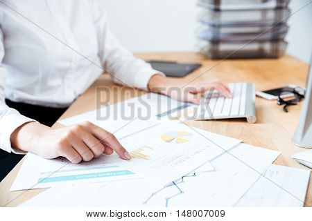 Cropped image of smart serious businesswoman pointing finger at work documents on the table and typing on keyboard in office