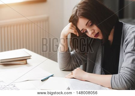 Young woman with writers block sitting in office at desk. Inspiration absence, desperation, creative crisis concept