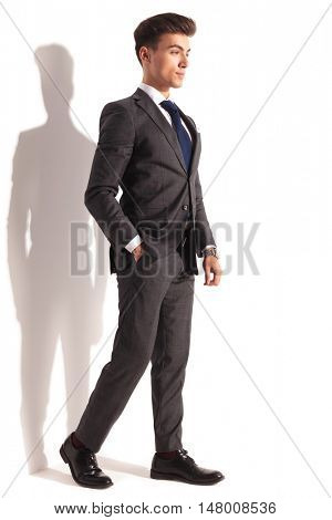 relaxed young business man walking in studio near white wall