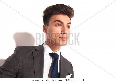 closeup picture of a young business man looking to side on white studio background