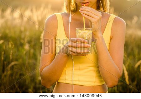 healthy young girl in sport yellow sport shirt and white headphones drinker refreshing lemonade with lemon slices on a transparent glass cup high on blurred background nature