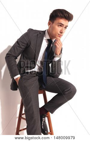 seated business man is thinking, on white studio background