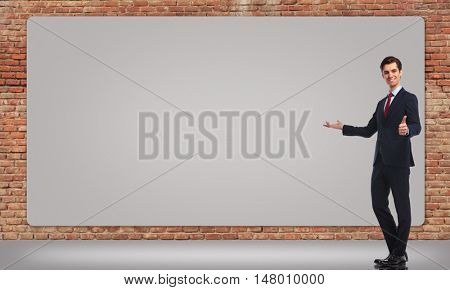 happy smiling business man presenting a big billboard and makes the ok thumbs up hand sign