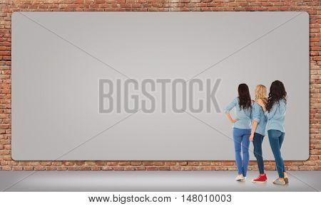 back view of three women looking at a big blank billboard on a brick wall