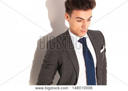 business man in suit and tie looking down to something on white background