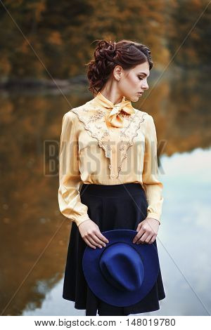 portrait of young brunette woman with hairstyle in elegant vintage blouse with bow and skirt with fashionable hat in hands near the river or lake in autumn park. Woman with hat in autumn park. Young beautiful model posing near the water.