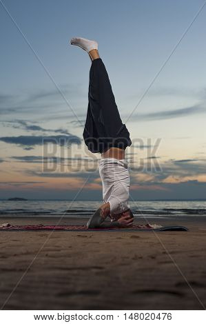 Full length shot young tattoo man practicing yoga on the beach at sunset. Headstand or shoulderstand exercise.