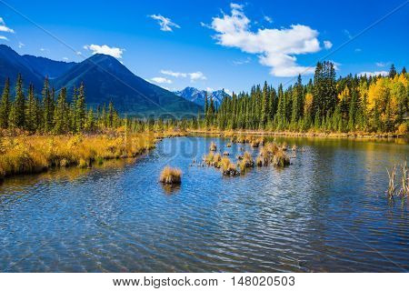 Shallow Lake Vermilion among the mountains and forests. Indian summer in the Rocky Mountains of Canada
