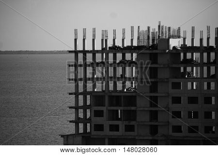Apartment building construction process ocean beach side in black and white monochrome photo