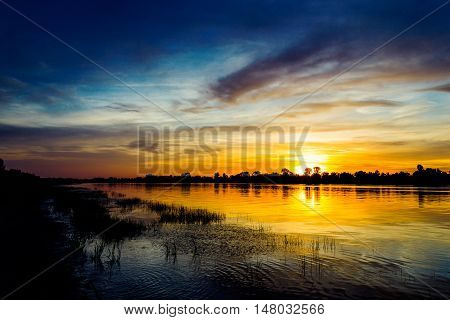 River at sunset and silhouettes of the bushes on the opposite bank