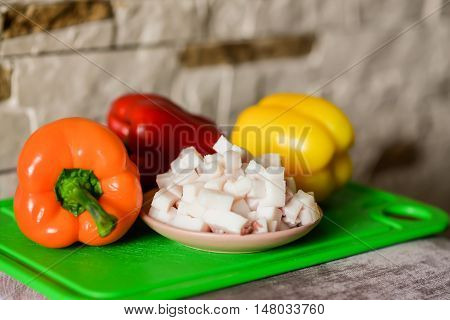 Lard cubes in small plate with colored bell peppers on green plastic board