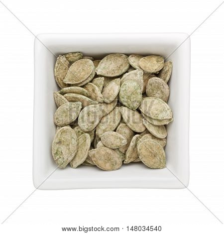 Green tea flavored roasted pumpkin seeds in a square bowl isolated on white background