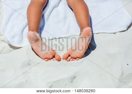 Close up of child feet on beach towel on tropical white beach