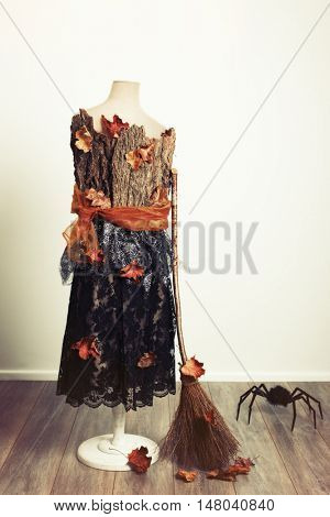 Halloween mannequin with fall leaves, witches broom and giant spider
