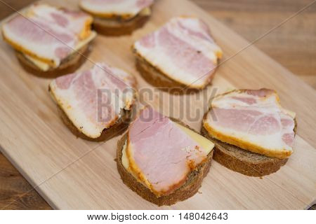 sandwiches with cheese and meat on a wooden board