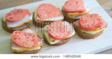 sandwiches with cheese meat tomato on a wooden board