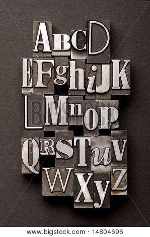 Alphabet mit einer Mischung aus Vintage-Buchdruck-Zeichen auf einem schwarzen strukturierten Hintergrund fotografiert.