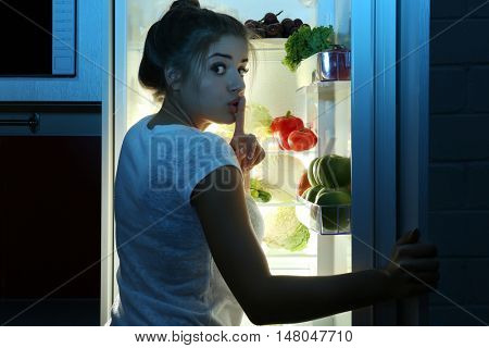 Beautiful girl searching for food in fridge. Hunger concept
