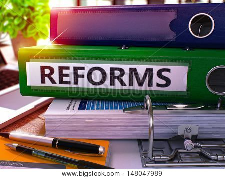 Reforms - Green Office Folder on Background of Working Table with Stationery and Laptop. Reforms Business Concept on Blurred Background. Reforms Toned Image. 3D.
