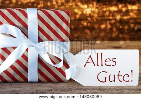 Macro Of Christmas Gift Or Present On Atmospheric Wooden Background. Card For Seasons Greetings, Best Wishes Or Congratulations. White Ribbon With Bow. German Text Alles Gute Means Best Wishes