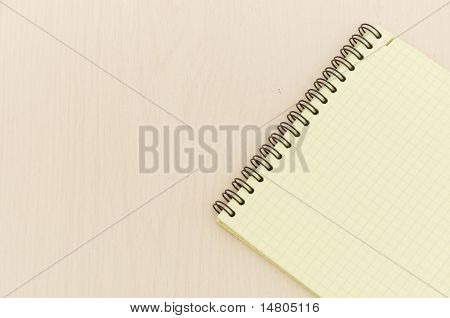 yellow note book on wooden table
