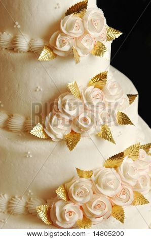 A soft white wedding cake with floral accents