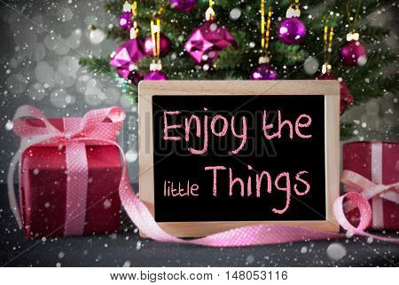 Christmas Tree With Rose Quartz Balls, Snowflakes And Bokeh Effect. Gifts Or Presents In The Front Of Cement Background. Chalkboard With English Quote Enjoy The Little Things