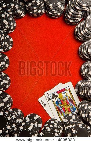 Black poker chips on red felt with Blackjack (21) hand