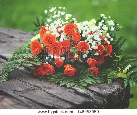 Beautiful bouquet of roses on wooden table outdoors