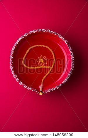single Clay diya lamp lit during diwali festival. happy diwali Greetings Card Design, Indian Hindu Festival of lights called Diwali