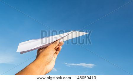 Hand holding white paper plane in bright blue sky.
