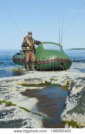 fisherman near the boat on the shore of the Barents Sea