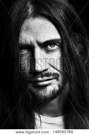 Black and white close up dark dramatic portrait of brutal brunet sullen handsom longhaired middle-aged man rock musician artist. Harsh tired sharp male gaze.