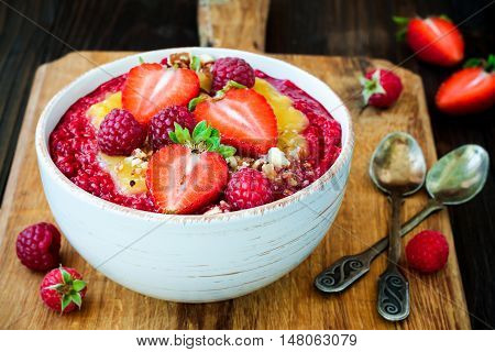 Healthy breakfast. Mango maca smoothie bowl topped with hazelnuts oat granola fresh berries and raspberry puree. Rustic style vintage silverware.