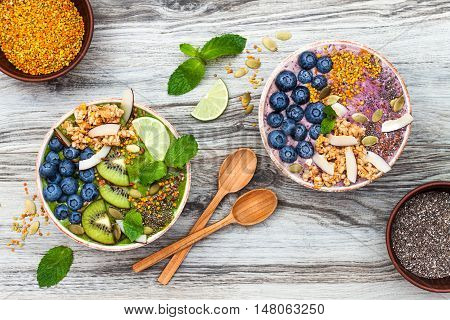 Acai and matcha green tea breakfast superfoods smoothies bowls topped with chia flax and pumpkin seeds bee pollen granola coconut flakes and blueberries. Overhead top view flat lay