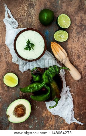Preparing avocado cilantro sauce for fish tacos. Lime crema in a bowl on vintage stone background. Recipe for Cinco de Mayo party. Top view.