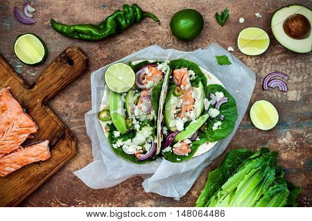 Preparing healthy lunch snacks. Fish tacos with grilled salmon red onion fresh salad leaves and avocado cilantro sauce on vintage stone background. Recipe for Cinco de Mayo party. Top view.