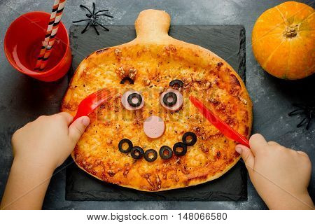 Child eating pizza in the shape of a pumpkin top view