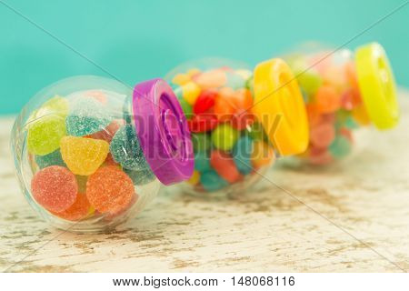 Three glass containers full of jellybeans on wooden table with blue background. Focus in the foreground
