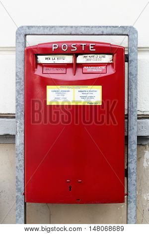 Milan, Italy - September 16, 2016: Red letterbox in Italy. Poste italiane is an Italian postal services provider. It was partially privatized by selling 35% of its shares to the public