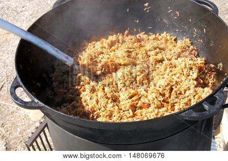 Cooking pilaf dish in outdoor. pilaf in a cauldron street food